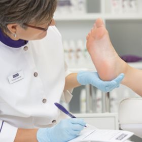 technician evaluates client feet before modern footlogix pedicure